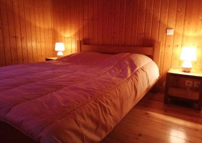 Chambre avec lit 2 personnes dans un grand chalet